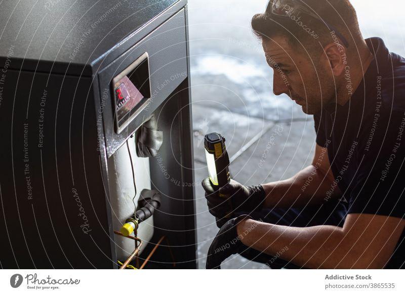 Mechanic with flashlight examining mechanism in workshop mechanic examine check repair machine tool man professional glasses headphones using job equipment
