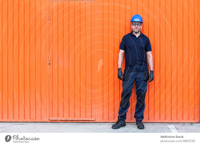 Male worker in hardhat standing near workshop cheerful confident friendly man professional mechanic positive wall adult male workman bright smile job happy