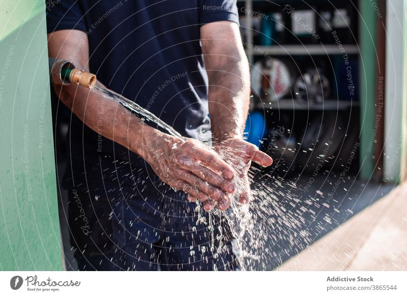 Mechanic washing hands in workshop worker repairman workman water professional clean tap service job occupation labor male maintenance dirty small business