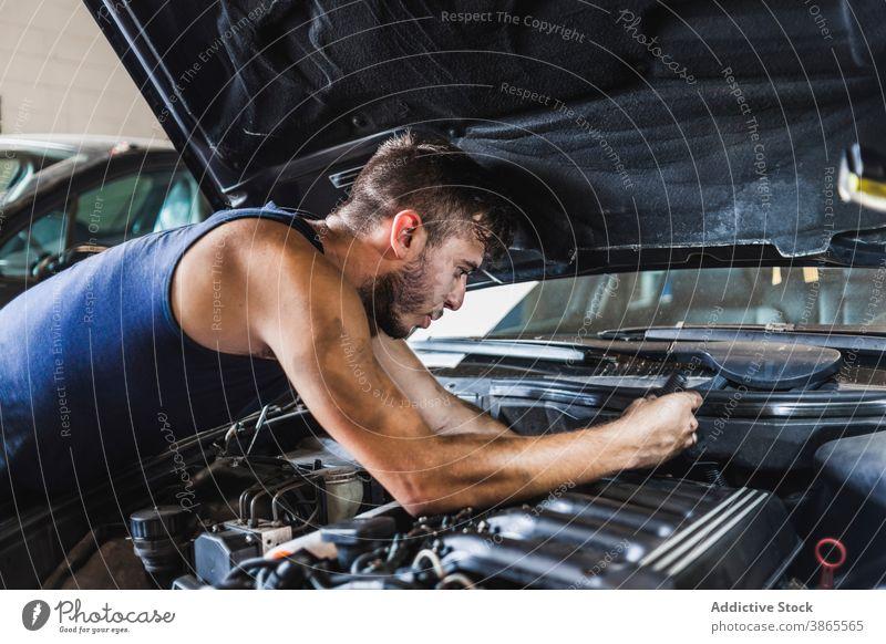 Male mechanic unscrewing engine of car man garage work dirty maintenance repair male fix vehicle transport occupation professional motor automobile screwdriver