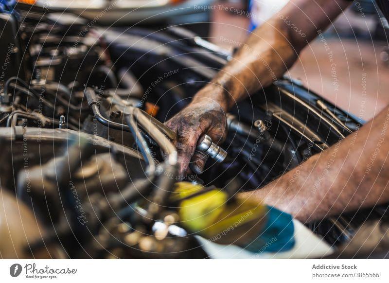 Crop technician with flashlight examining car motor man mechanic check engine garage illuminate work repair male vehicle transport service job fix busy industry