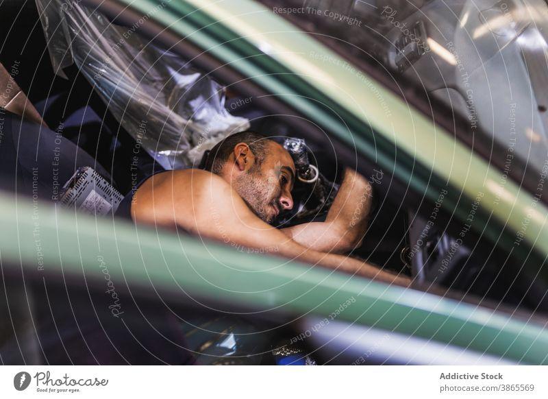 Male technician checking car dashboard man garage work seat modern service male adult lying passenger vehicle transport job auto fix repair inspect mechanic