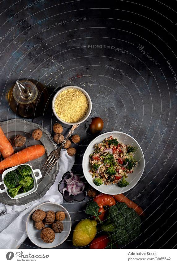 Vegetarian couscous salad on table with ingredients vegetable vegetarian bulgur tabbouleh healthy food bowl homemade various fresh meal delicious organic dish