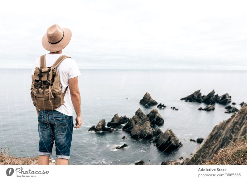 Man standing on hill and enjoying seascape traveler observe viewpoint man explore wanderlust adventure wonderful male scenery rocky mountain cloudy sky nature