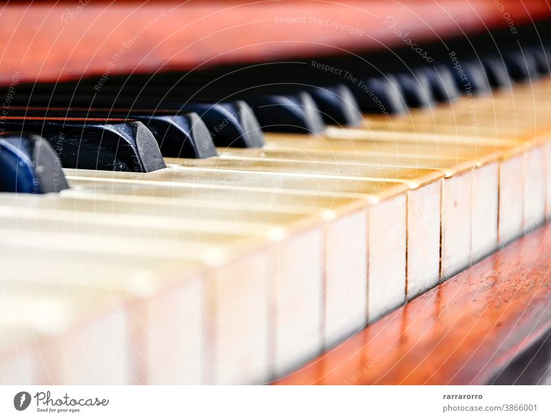 Close up of the keys of an old worn piano. keyboard instrument musical detail black key wood ivory antique selective focus art vintage white classical sound