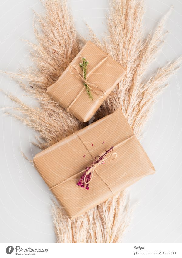 Gift boxes wrapped in craft paper with dried flowers autumn gift zero birthday christmas background give surprise present concept waste pampas stack grass