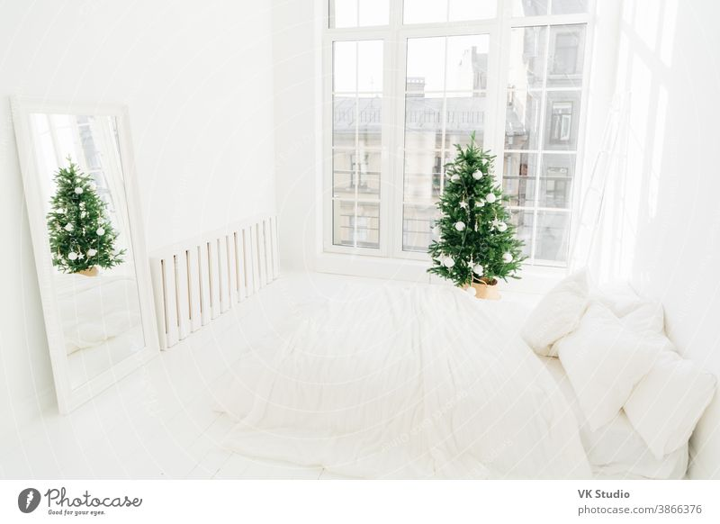 Comfort, home and Christmas Eve concept. Bedroom with white soft bed, mirror, big window for light coming in room, decorated New Year tree and ladder. Holiday decoration.