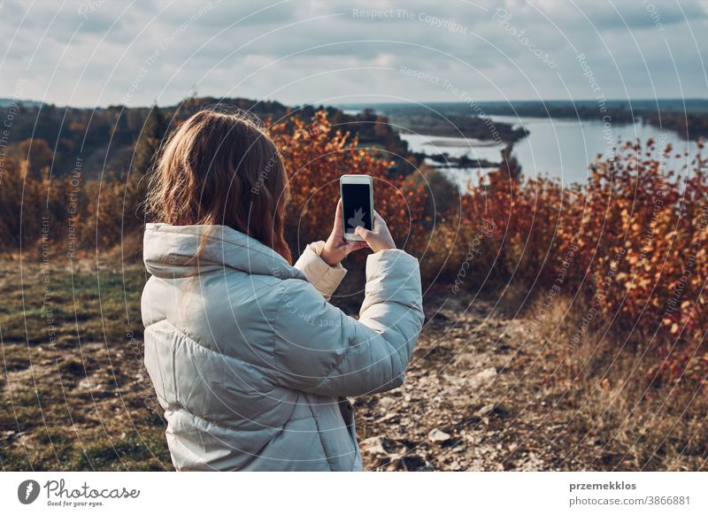 Back view of young woman taking photos of landscape with smartphone during trip on autumn sunny day take selfie outdoors taking selfie destination hiking