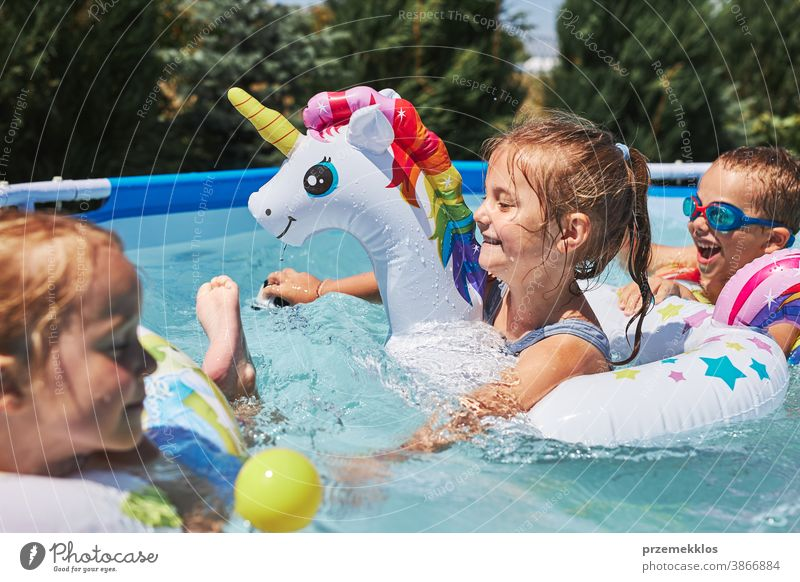Children playing in a pool in a home garden. Kids having fun playing together on a summer sunny day authentic backyard childhood children family happiness happy