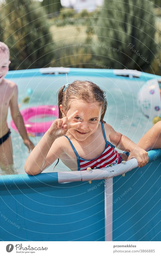 Happy girl making V sign gesture playing in a pool enjoying splashing having fun with siblings on a summer sunny day authentic backyard childhood children