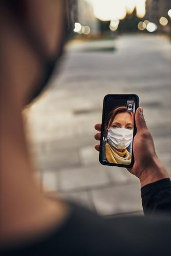 Young man having video call with her mother standing outdoors in the street in the evening wearing the face mask to avoid virus infection and to prevent the spread of disease in time of coronavirus