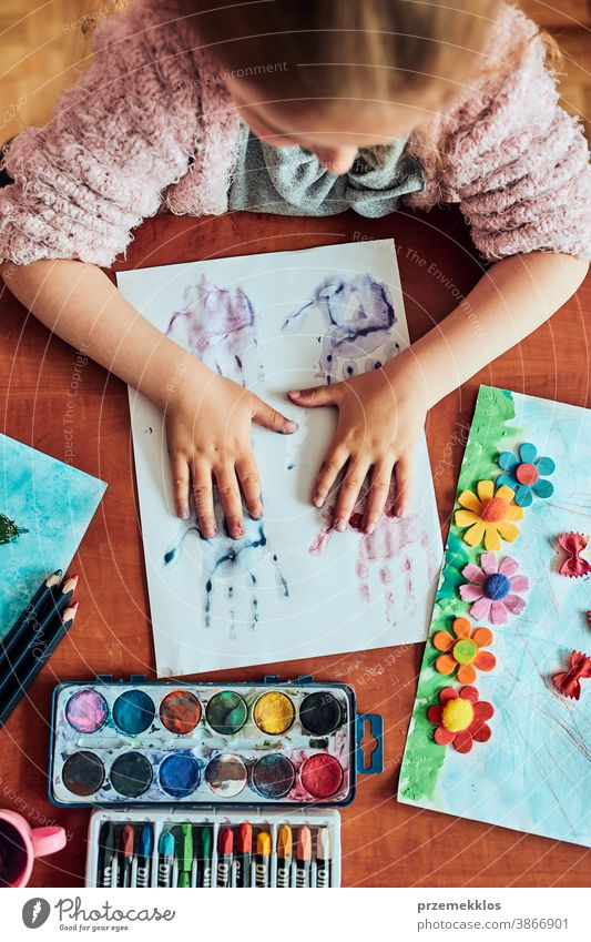 Little girl preschooler painting a picture using colorful paints and crayons. Child having fun making a picture during an art class in the classroom child dye