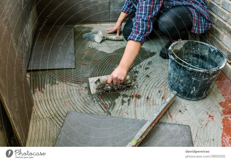 Female mason laying tiles on a terrace unrecognizable woman workman tiling floor hand detail reform imitation cement tile spread tiler glazed terrace working
