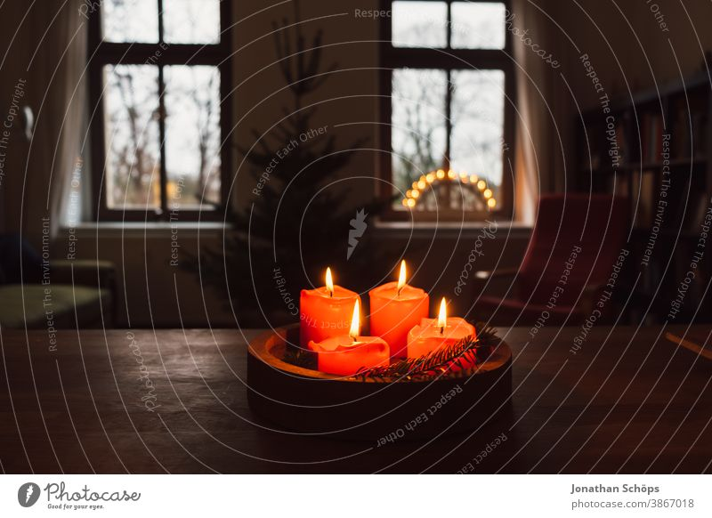 advent wreath with burning red candles standing on wooden table in living room with candle arch in window Bright Christianity Christmas Christmas & Advent