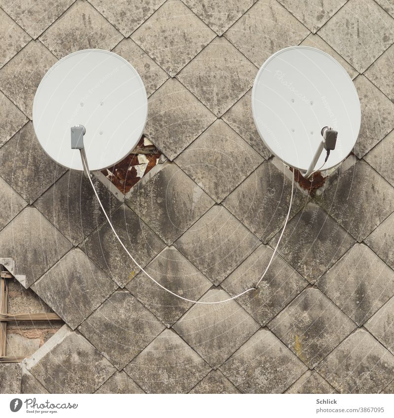 Two parabolic antennas in a dirty facade made of asbestos fibreboards remind of a pair of ears Parabolic antennas 2 Couple find out facade panels