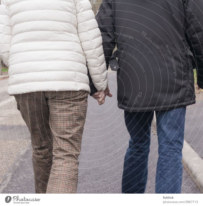 love older couple in winter clothes holding hands and walking on the street rear view Love Couple Lovers hold hands senior citizens Going Street Asphalt Jackets