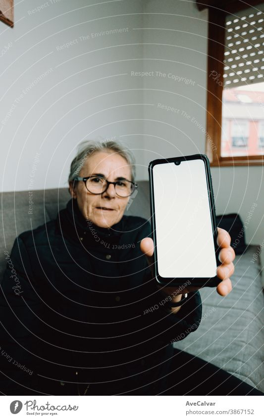 Old woman showing a mobile phone with a white screen with copy space person elderly grandmother copyspace mature senior happy older retired retirement call lady