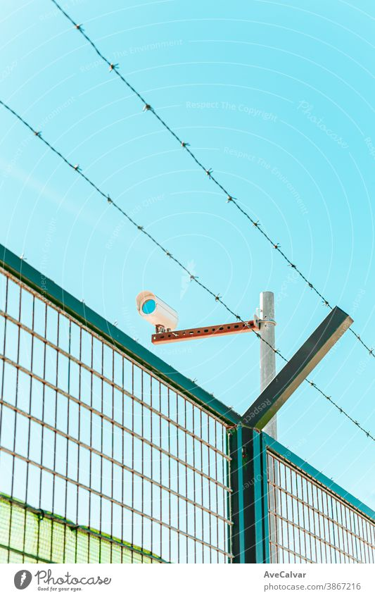Minimalistic and colorful shot of a surveillance camera with a wall and a barbed wire private protection safety system guard lens security video cctv control