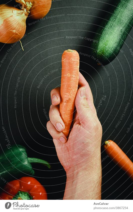 Hand grabbing a carrot surrounded by vegetables with a black table culinary kitchen cuisine cooking chopping board preparation knife cutting board food wooden