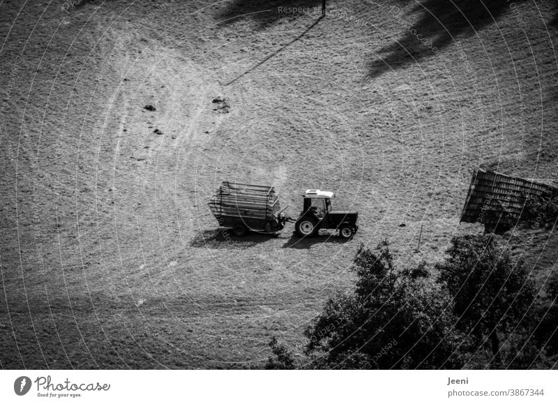 Small tractor with trailer on an alpine meadow in the mountains from a bird's eye view Tractor Trailer Alpine pasture Alps from on high Mountain Slope