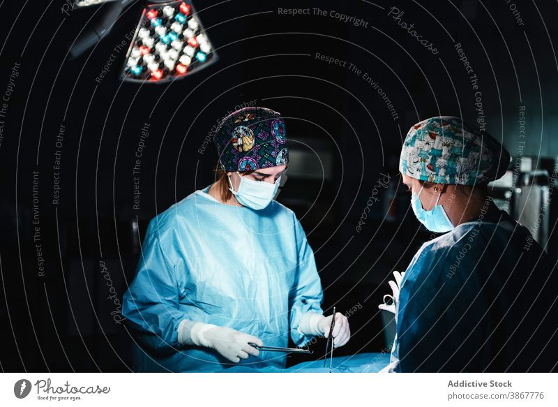 Medics doing surgery in hospital surgeon operating theater medic team together thread tool assistant stitch nurse operation instrument work skill job care