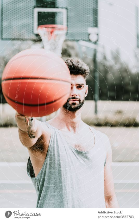 Young man with basketball ball on sports ground confident player game streetball beard young serious training playground athlete activity lifestyle sportsman