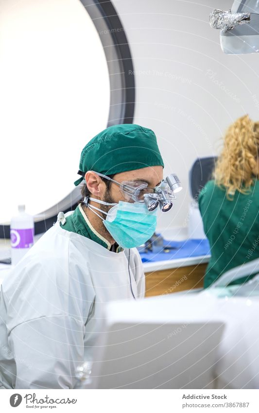 Male dentist in medical mask and glasses in clinic dental oral treat man doctor binocular stomatology dentistry professional work job health care staff uniform