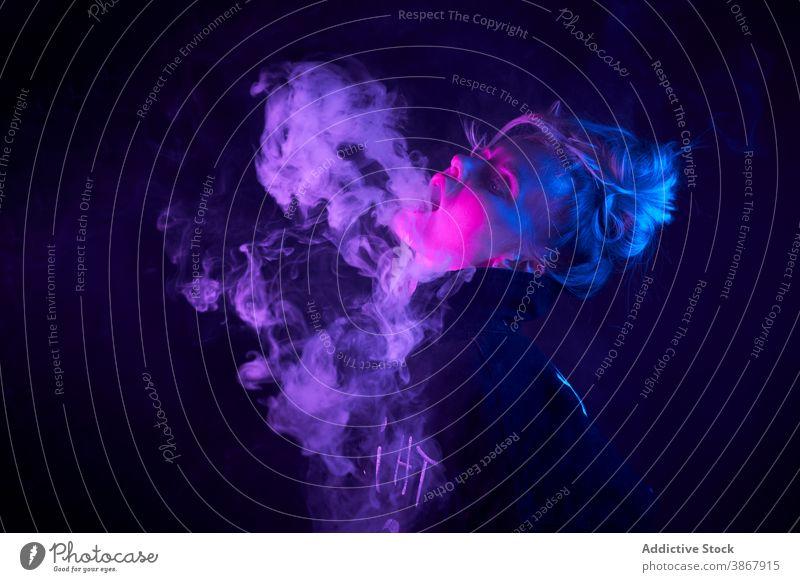 Expressive woman smoking in dark studio vape smoke e cigarette neon light steam cool female style nicotine smoker habit confident young bad unhealthy addict