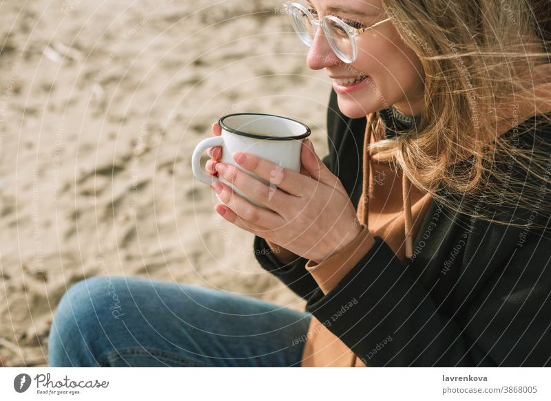 Portait of young adult female with enamel mug with hot drink sitting on a beach woman cup autumn winter happy tea lifestyle smiling morning cheerful seasonal