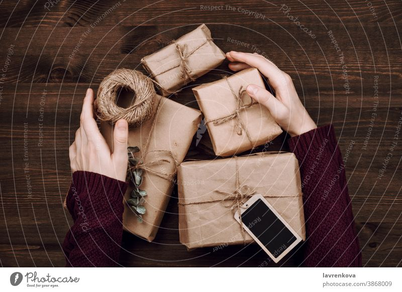 woman's hands in sweater holding wrapped presents and roll of string on wooden background sustainable beautiful birthday box celebration christmas craft