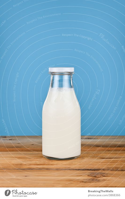 Close up one glass bottle of milk over blue Milk yogurt yoghurt fresh full closeup background table low angle view side front dairy white food ingredient drink