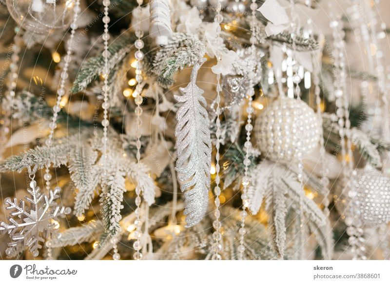 Christmas tree decoration: Christmas glass toys, flickering garlands. concept: an example of the interior of a living room of a residential building. image for greeting card or poster