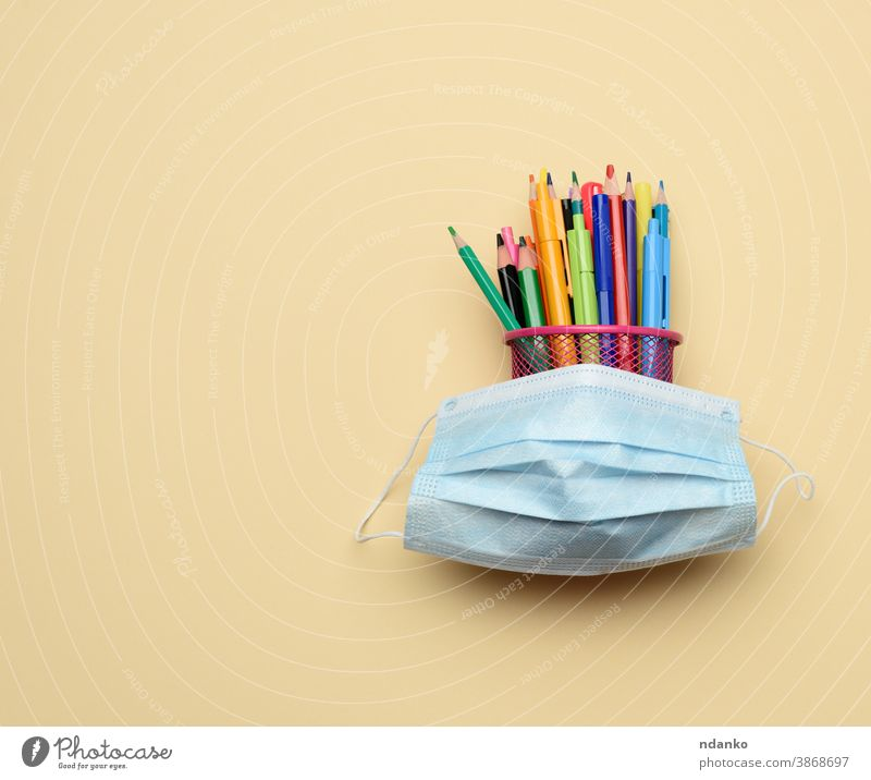 disposable medical mask and multi-colored pencils and pens in a metal bucket on a beige background pandemic prevention protective quarantine safe safety school