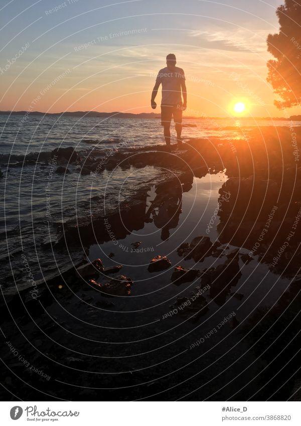Man silhouette in the sunset while walking on rocky beach dark body tranquility seascape dawn sundown idyllic boy Orange twilight beautiful coastline adult