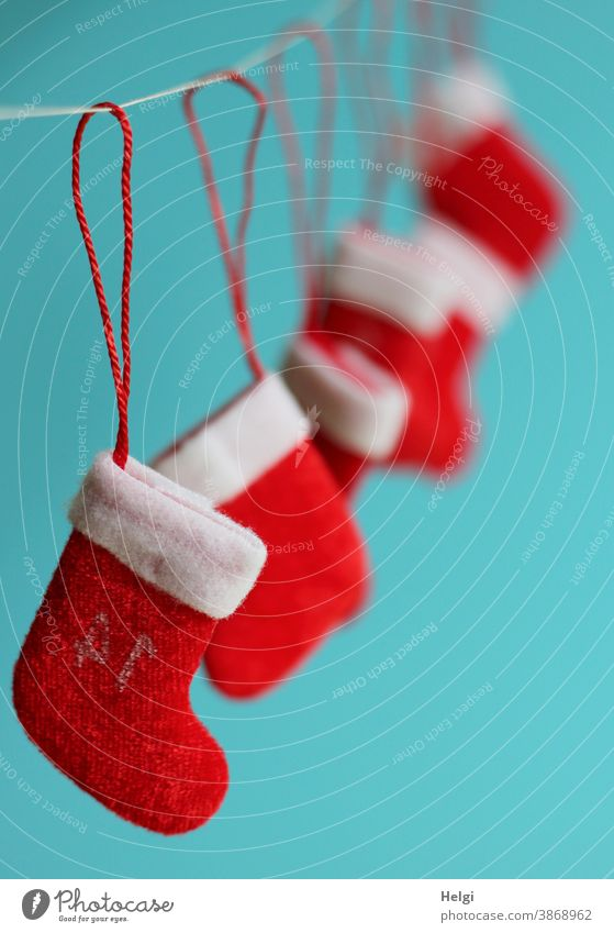 several small Santa boots hang on a rope in front of a turquoise background Santa's boots Christmas Santa Claus Advent Christmas & Advent Christmas decoration