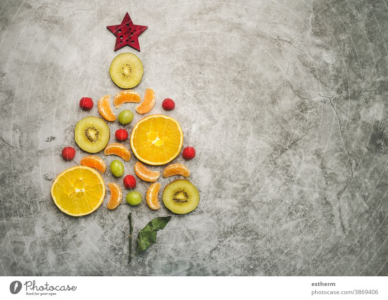 Christmas concept background. Pieces of fruit in the form of a christmas tree fruits orange healthy food diet christmas dessert kiwi slice fresh tangerine