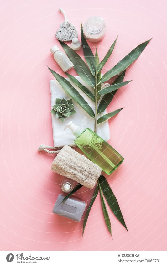 Eco friendly beauty with green bamboo leaves. Skin care bathroom accessories, natural sisal brush, wooden comb, soap, reusable make up removal pads. Zero waste. Top view. Natural and pastel col