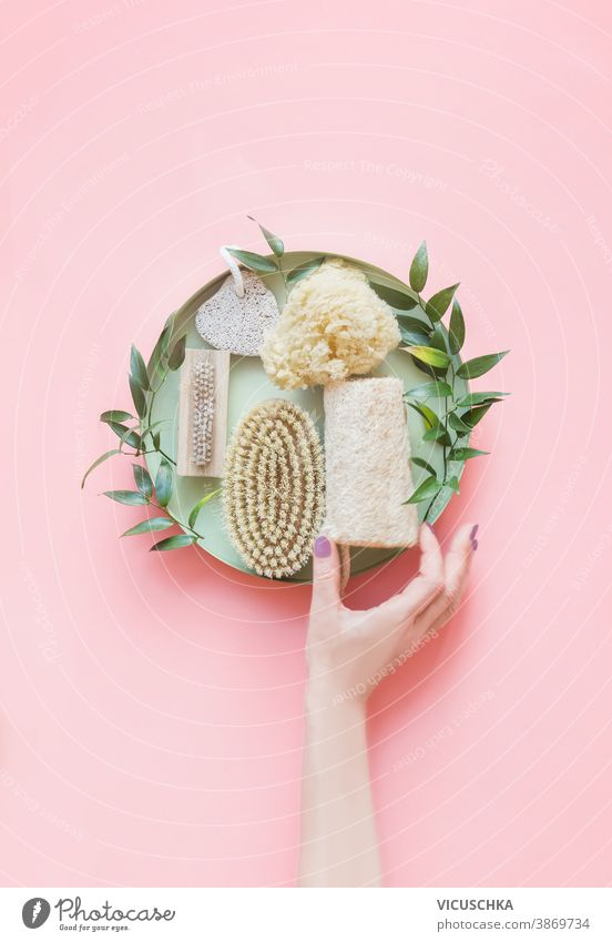 Women hand holding eco friendly beauty and skin care bathroom accessories.  Natural sisal brush, wooden comb, soap, reusable make up removal pads. Zero waste. Top view. Natural and pastel colors.