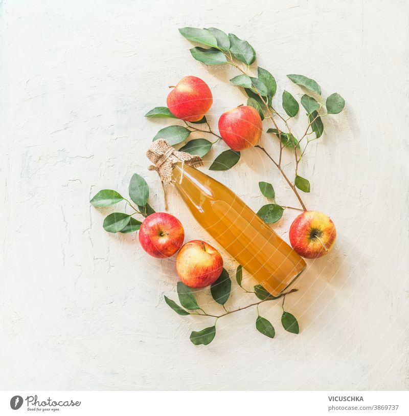 Composing with homemade apple juice in glass bottle with apples and green leaves on white background. Top view homemade food apple tree twigs pattern top view