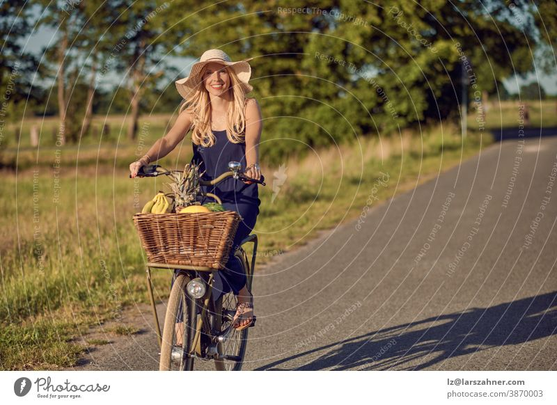 Portrait of a beautiful woman smiling happy while wearing a striped shirt and riding a bicycle in the countryside in a sunny day face portrait summer