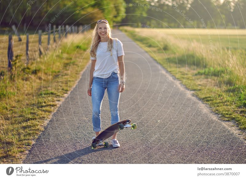 Attractive athletic blond woman with her skateboard backlit by the evening sun on a rural road between fields smiling at the camera middle-aged fit playing