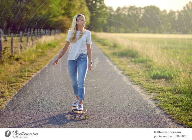 Fit active middle-aged woman playing on her skateboard approaching the camera along a narrow rural road with a happy smile backlit by the evening sun fit blond
