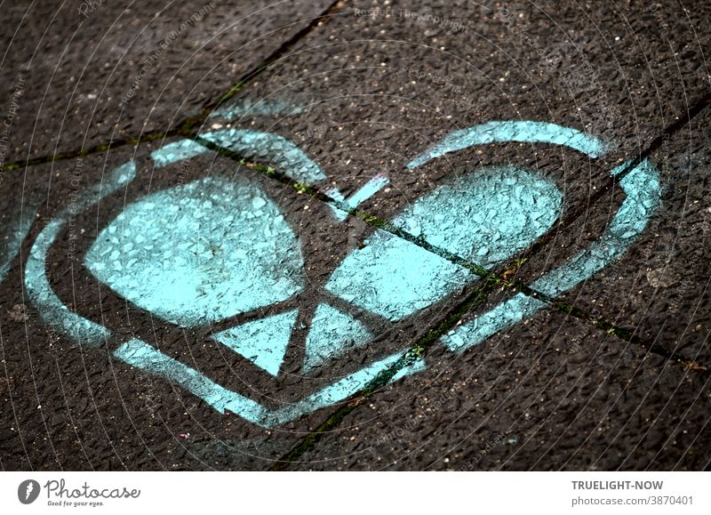 The blue heart. The cold heart. The heart of stone. The Divided Heart. The Heart of ice. A graffiti heart in blue and black sprayed on grey concrete slabs.
