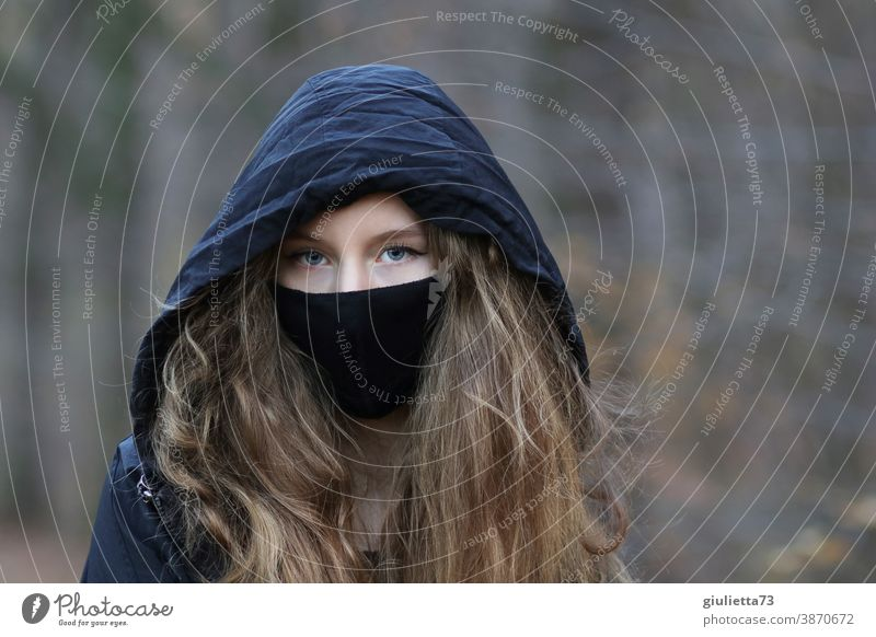 Portrait of a teenage girl with hood and mouth-nose cover, mask I corona thoughts portrait Day Exterior shot Colour photo Puberty Emotions Long-haired