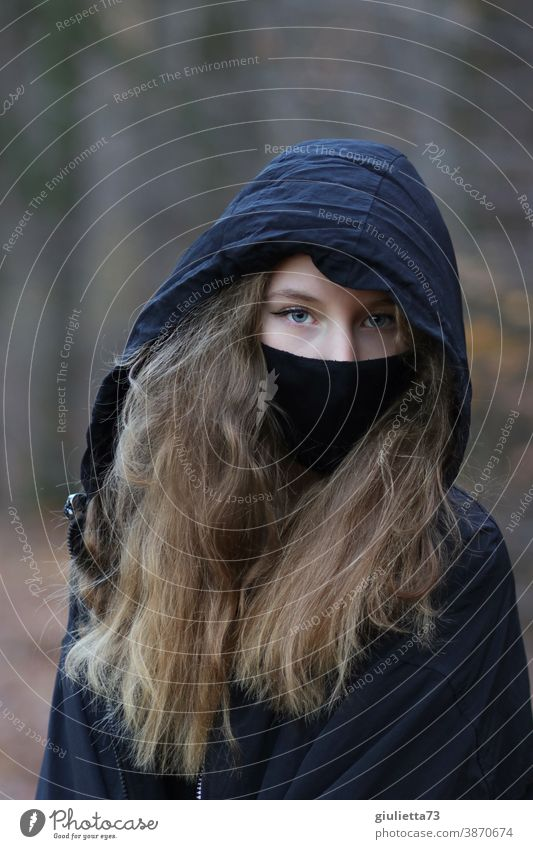 Portrait of a teenage girl in black, with hood and mouth-nose cover/ mask I corona thoughts flu covid-19 somber Epidemic COVID Risk of infection coronavirus