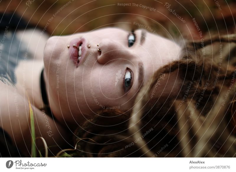 Lateral portrait of a young woman with dreadlocks and tattoos, lying in the wood Woman Dirty Blonde tattooing Jewellery Piercing earring Concealed Direct Nahe