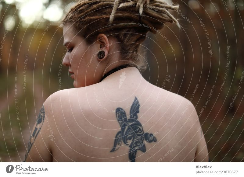 Portrait of a young woman with dreadlocks and tattoos in the forest Woman Dirty Blonde tattooing Jewellery Piercing earring Upper body Naked Concealed Direct