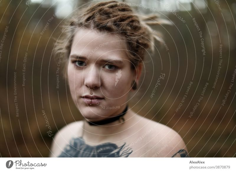 Portrait of a young woman with dreadlocks and tattoos in the forest Woman Dirty Blonde tattooing Jewellery Piercing earring décolleté Upper body Naked Concealed