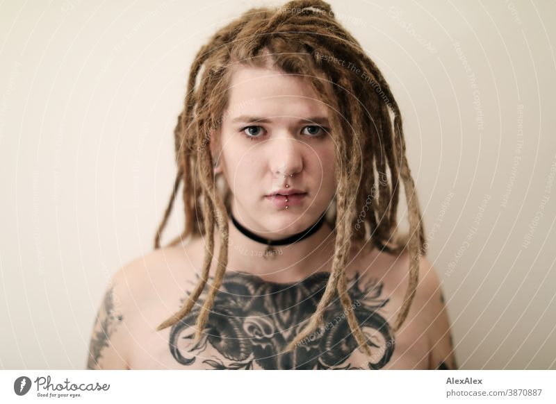Portrait of a young woman with dreadlocks, who has a large tattoo of an ox head on her décolleté Woman Dirty Blonde tattooing Jewellery Piercing earring Chest