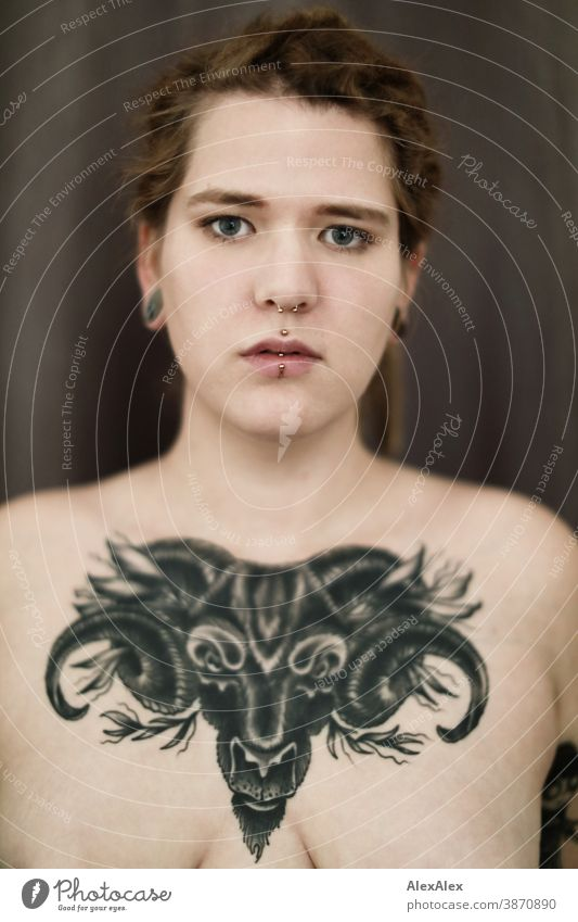 Portrait of a young woman, who has a large tattoo of an ox head on her décolleté Woman Dirty Blonde tattooing Jewellery Piercing earring Chest Upper body